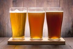 Surtido de vidrios de cerveza en una tabla de madera Fotos de archivo