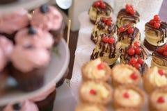 Surtido delicioso del postre con las magdalenas, tortas con la pasa roja y, tartas del huevo de las natillas con el foco selectiv Foto de archivo libre de regalías