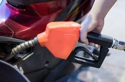 Surtidor de gasolina que llena en la gasolinera fotos de archivo