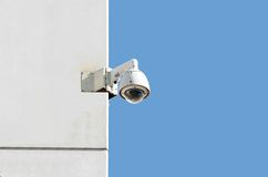 Surveillance camera. At a white wall with blue sky background Royalty Free Stock Photo