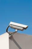 Surveillance camera. Closed circuit tv surveillance camera against a light blue sky Stock Image
