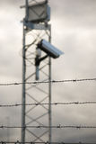 Surveillance camera and barbed wire Stock Photos