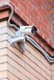 Surveillance camera on brick wall Stock Images