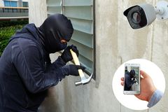 Surveillance Camera capture and record caught Masked thief with hammer and hand holding Mobile Phone Detecting on application stock image
