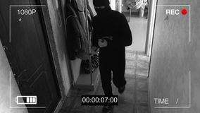 Surveillance camera caught the robber in a mask with a crowbar stock footage