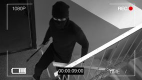 Surveillance camera caught the robber in a mask with a crowbar.  Royalty Free Stock Photos