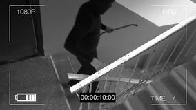 Surveillance camera caught the robber in a mask with a crowbar.  Stock Photo
