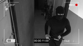 Surveillance camera caught the robber in a mask with a crowbar.  Stock Photos