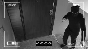 Surveillance camera caught the robber in a mask with a knife.  Stock Photos