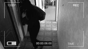 Surveillance camera caught the robber in a mask running off with a bag of loot.  stock image