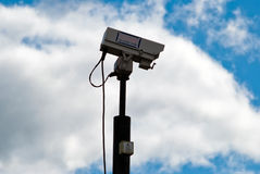Surveillance camera in front of sky V2. Security camera with clouds and sky Royalty Free Stock Photo