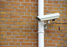 Surveillance Camera mounted on Yellow Brick Wall Stock Photo
