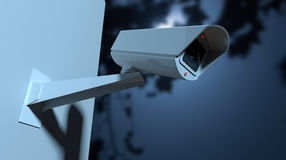 Surveillance Camera In The Night-time. A white wireless surveillance camera with illuminated lights mounted on a wall in the night-time with copy space Royalty Free Stock Image