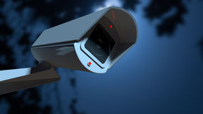 Surveillance Camera In The Night-time. A white wireless surveillance camera with illuminated lights mounted on a wall in the night-time with copy space Stock Photo