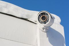 Surveillance camera. Surveillance camera on a white wooden dirty wall under a roof covered with snow stock images