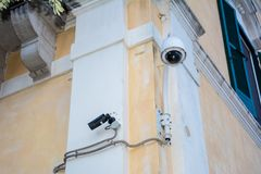 Surveillance camera on a wall of a building stock photo