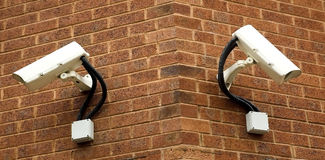 Surveillance Cameras. Mounted on a wall looking down Royalty Free Stock Image