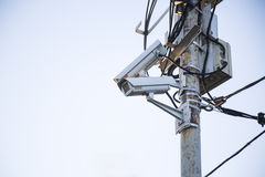 Surveillance cameras on a post on the street against blue sky. royalty free stock images