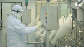Pharmaceutical Production Line Worker at Work. Robotic arm lifting ampules at packaging line in pharmaceutical factory Stock Photos