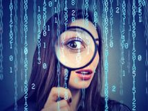 Surveillance of cyber crime concept. Curious woman looking through a magnifying glass and computer binary code background
