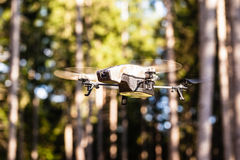 Surveillance drone in the wild. A small spy quad copter scout drone flying through the trees in a forest royalty free stock photos