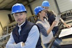 Surveillant dans une usine industrielle avec des employés Photo libre de droits