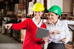 Surveillant féminin avec le collègue à l'entrepôt Photos libres de droits