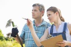 Surveillant féminin expliquant quelque chose au jardinier à la pépinière d'usine photo stock
