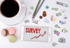 Survey, Business Concept. Mobile phone and coffee cup on a white office desk Stock Image