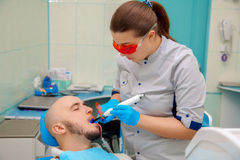 On survey at the dentist checks the teeth of the patient Stock Photo