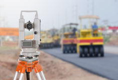 Survey equipment theodolite on a tripod. with road under constru Stock Photo