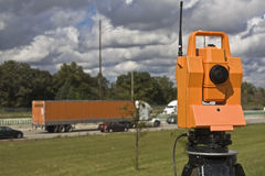 Survey on the highway. Orange theodolite and semi-truck stock photography