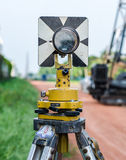 Survey instrument set on a tripod in the field. Traverse prism for survey on dirt road stock photo