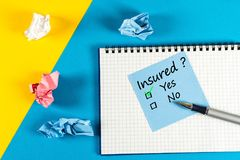 Survey with question Insured, Yes or no. Message at notepad at yellow and blue table, insurance agent.  royalty free stock photo