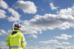 Surveying engineer with measuring instrument. Surveyor working with measuring instrument, total-station measuring horizon for future construction works. blue sky Royalty Free Stock Images