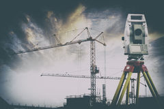 Surveying instrument, and building site. Surveying instrument, cranes and scaffolding constructions Royalty Free Stock Photography