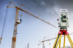 Surveying measuring instrument and industry. Surveying measuring instrument with large construction cranes in background, total-station instrument Royalty Free Stock Photo
