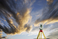Surveying measuring instrument and sunset. Surveyors measuring instrument, total-station aimed at the horizon for future construction projects Royalty Free Stock Images