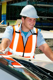 Surveyor. Studing Plans To A Construction Site On The Hood Of His Truck royalty free stock image