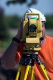 Surveyor. A surveyor at a construction site peering through a theodolite taken with narrow depth of field stock photos