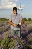 Surveyor adjusting its instrument in a field of lavender. During the sunny day royalty free stock photo