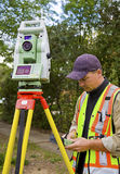 Surveyor checks his work. Surveyor examines his calculations on construction project Royalty Free Stock Photo