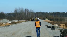 Surveyor or chief inspects and writes information during a stage of road building before laying of pavement material or. Engineer inspector looks and writes data stock video