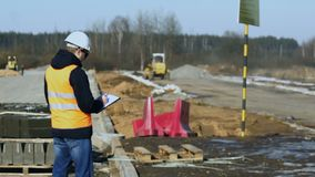 Engineer inspector looks and writes data during a phase of road construction before laying of pavement material or. Surveyor or chief inspects and writes stock video footage