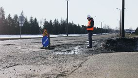 Engineer or builder looks, inspects the road pits and writes notes to tablet, sign of repair work is on a curb asphalt. Surveyor or chief looks and writes data stock footage
