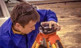 Surveyor. Engineer surveyor adjusts the device to determine the coordinates. South Kazakhstan region, in June 2015 royalty free stock photos