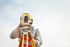 Surveyor engineer making measure with cloud background. Surveyor engineer making measure carefully with cloud background royalty free stock image