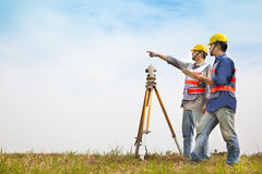 Surveyor engineer making measure with partner. On the field royalty free stock photography