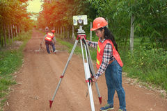 Surveyor or Engineer making measure with partner on a field. Surveyor or Engineer making measure by Theodolite and prism reflector with partner on the street in Stock Photo