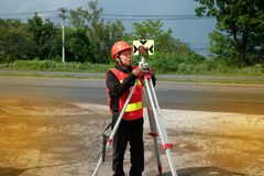 Surveyor or Engineer setting measure prism reflector on the highway. Surveyor or Engineer setting measure prism reflector on the highway in a field royalty free stock photo